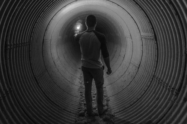 Mann geht im Tunnel mit Licht voran
